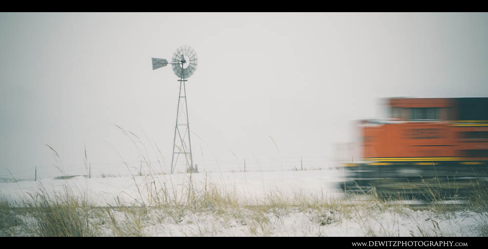 129BNSF Train Flashes Past Wyoming Windmill