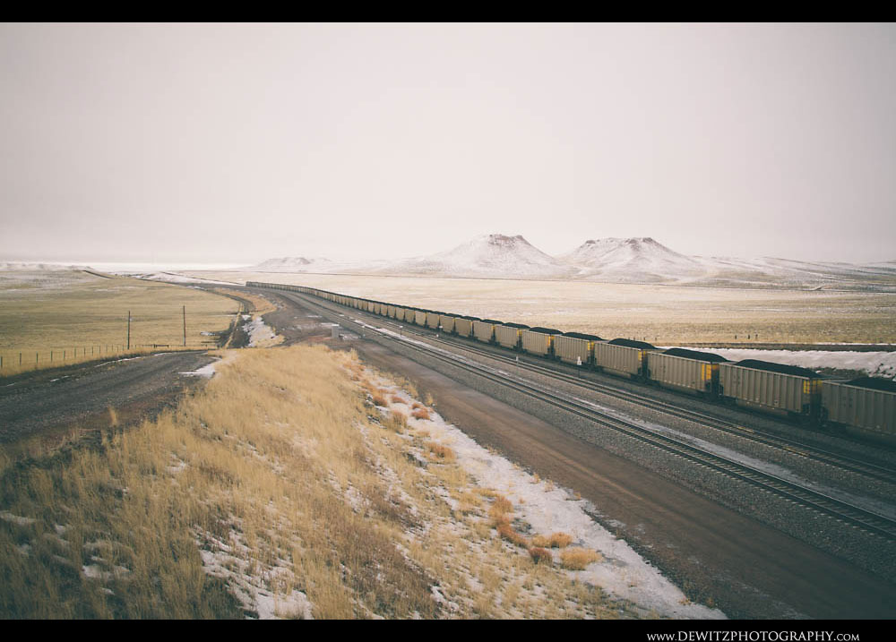 305Large Hills Stand Above the Grasslands as a Train Stretches Across the Landscape