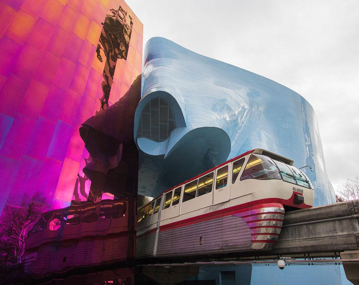 Nick Benson Mono Rail Going Through Neon Glass Buildings
