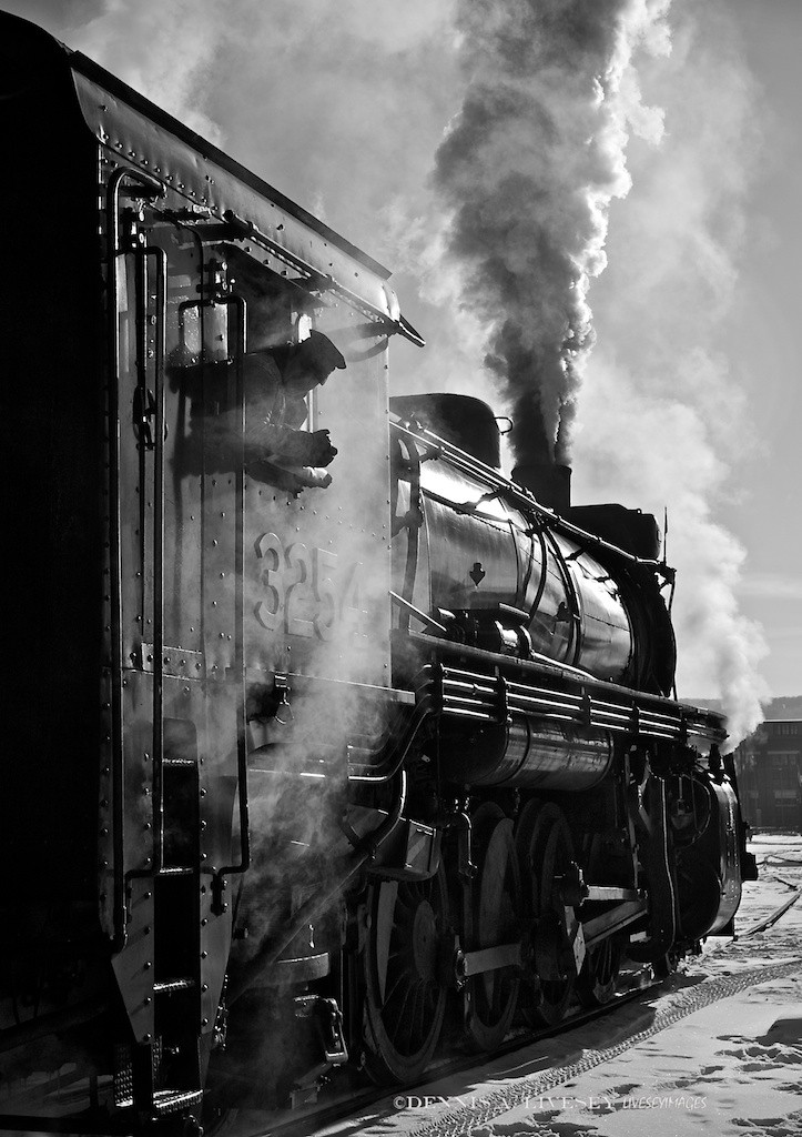 On January 17th, 2009, I took this image of Steamtown's CN No. 3254. The temp was around 10F, fairly new snow was on the ground and, most astonishingly, the sky was clear. Being winter, the sun was low and with the clear sky and snow, the light was utterly amazing for Scranton! I kept finding these exciting shots looking into the sun. The front lit was good, don't get me wrong, but the back lit stuff had my fun meter pinned. I think Gordon Willis would approve for not only can't you see engineer Aaron Stout's eyes, you can't see his face! The light, the steam, the vapor, the black engine and the white snow are so contrasty, I even like to think Conrad Hall would smile.