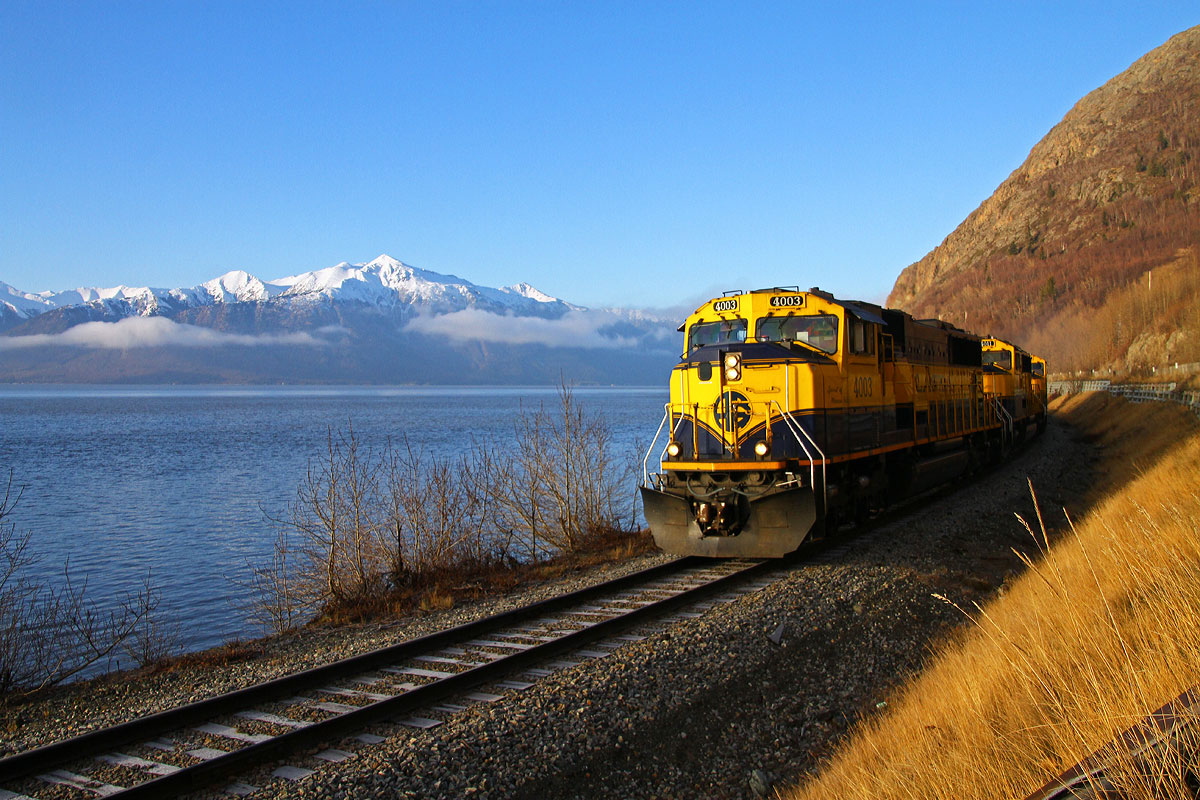 An Alaska RR empty lumber trains rolls along Turnagain Arm, in the background are the Kenai Mountains.