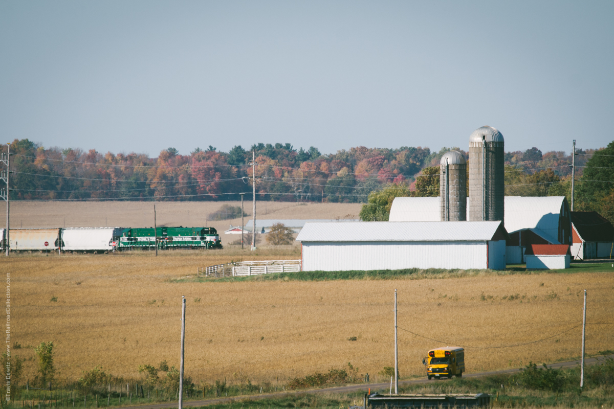 A typical Wisconsin countryside autumn scene. School bus drives down a long country road as a Wisconsin Northern train travels pasts the farms along its route to Chippewa Falls.