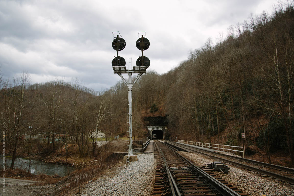 The Norfolk and Western Railway's coal hauling right of way once followed the course of the Tug River between Welch and Davy. In 1903, the railroad started a major rebuilding project to straighten out portions of the Pocahontas Division and prepare for future double tracking. Just a year later, two tunnels were constructed roughly a mile norwest of Welch, known as Hemphill. Hemphill originated as a name of a siding, likely named after Secretary of the N&W, A.J. Hemphill in 1894, which eventually evolved into a community. The two tunnels named Hemphill Tunnel No. 1 and No. 2 respectively were cut through the Appalachian Plateaus Physiographic Province, a region characterized by deeply incised plateaus underlain by flat-lying sedimentary rock. The railroad grade was raised during this realignment to avoid the common flooding of the Tug Fork which it crosses three times in this short stretch. The realignment shaved off 2.4 miles from the previous wandering Tug Fork route. Double tracking was completed here in 1909. The N&W CPL Signal can be seen by trains exiting the west portal of tunnel no. 2 that guards Farm, a well known railroad location where a large coaling tower still stands. Today, helpers wait assignments to shove heavily loaded coal trains east up the steep steady grade.